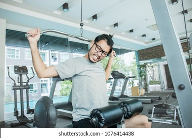 Attractive young asian nerd man working out with exercise machine