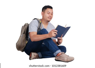 Attractive young Asian student reading book while sitting on the floor, isolated on white, smiling happy