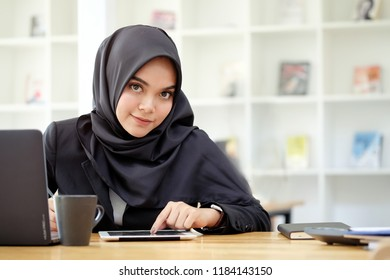 Attractive young Asian wearing dark hijab working with her tablet.