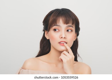 Attractive young asian woman applying lip balm on a white background