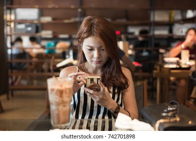 Attractive young asian woman checking her news feed or messaging via social networks, smiling, sitting in coffee shop during free time.