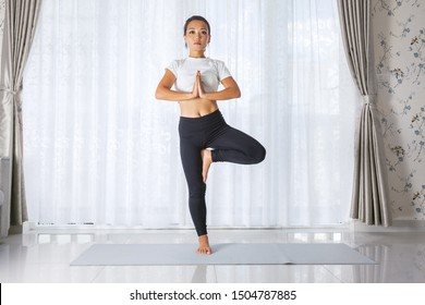 Attractive young asian woman exercising and sitting in yoga tree position while resting at home