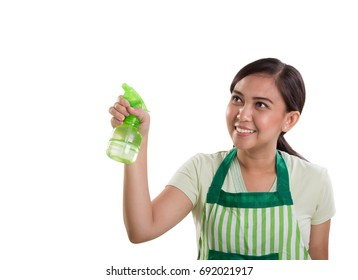 Attractive young Asian woman holding a clear spray bottle pointed at copy space on white background