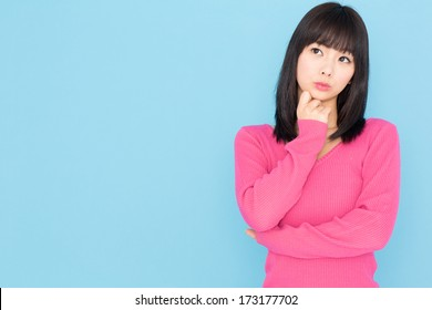 attractive young asian woman isolated on blue background