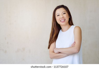 Attractive young Asian woman smiling while standing with her arms crossed in front of a wall outside