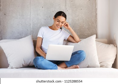 Attractive young asian woman using laptop computer while sitting on a couch at home