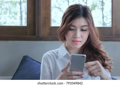 Attractive young Asian woman using mobile smart phone at living room.