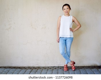 Attractive young Asian woman wearing a blouse and jeans smiling while standing with her hand on her hip in front of a wall outside