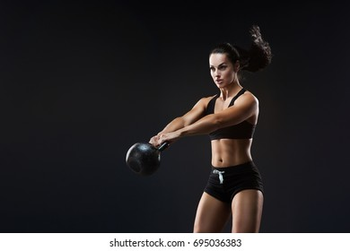 Attractive young athlete with muscular body exercising cross fit. Woman in sportswear doing cross fit workout with kettle bell on dark background.