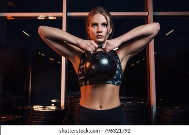 Attractive young athlete with muscular body exercising crossfit. Woman in sportswear doing crossfit workout with kettle bell at the gym