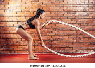 An attractive young and athletic girl using training ropes in a gym. on the background wall of red brick.