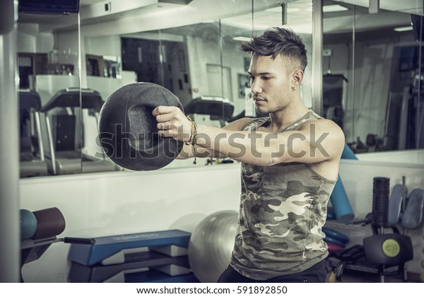 Attractive young athletic man exercising in gym, working out using kettlebell