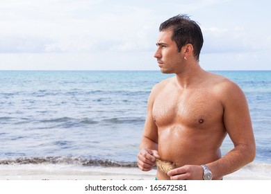 attractive young athletic man on the beach in summer outdoor vacation