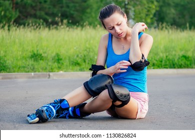 attractive young athletic slim brunette woman in pink shorts and blue top with protection elbow pads and knee pads on roller skates sitting on the asphalt in the park . fall concept