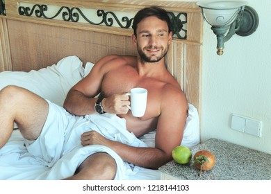 Attractive young bachelor man lying in bed with naked muscular torso and a sexy look with a smirk on his handsome face enjoing his morning. isolated on white background with big biceps and chest