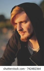 Attractive young bearded man with black hood on. Portrait.