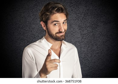 Attractive young bearded man pointing at camera