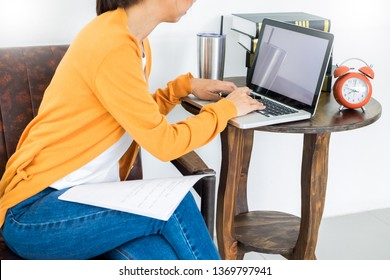Attractive Young beautiful entrepreneur Woman smiling and looking at laptop screen, Working from Home