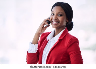 Attractive young black businesswoman smiling at the camera while talking on her mobile phone that she is holding in her right hand, all while looking good in her red and white outfit.