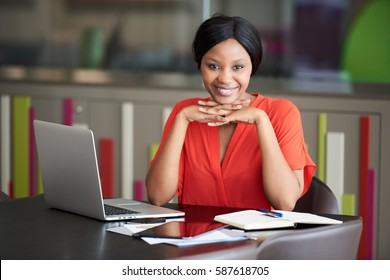 Attractive young black female student smiling at the camera while supporting her head with her hands that are interlocked, while seated at the conference table at work.