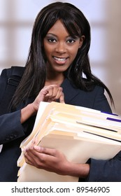Attractive young black woman holding file folders at school or office.