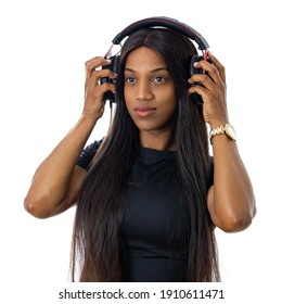 Attractive, young black woman listening to music on with headphones. Wearing a casual black t-shirt. Isolated studio shot with white background.