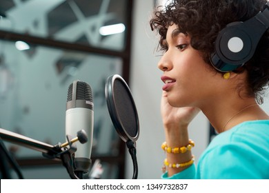 Attractive Young Black Woman Singing Into Microphone in Recording Studio Session. African American Female and podcast host with curly hair in Radio Show Talking to Microphone while wearing headphones