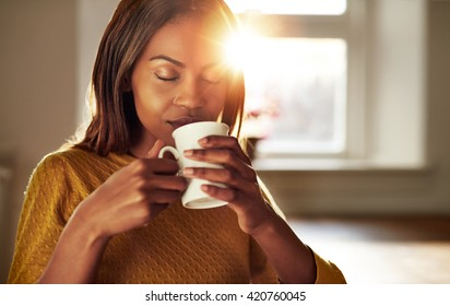 Attractive young black woman sitting at a table at home backliot by a bright sun enjoying a cup of fresh coffee with her eyes closed in bliss