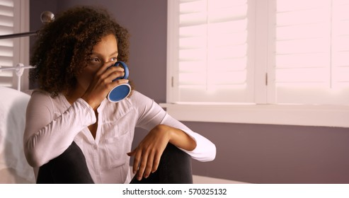 Attractive young black woman thinking and drinking from coffee cup.