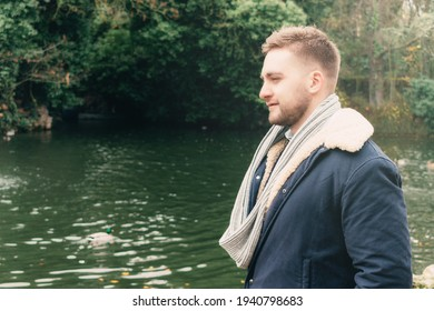 a attractive young blond bearded man by a lake