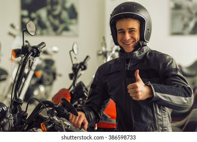 Attractive young blond man in black leather jacket and helmet is looking at camera, showing Ok sign and smiling while sitting on a motorbike