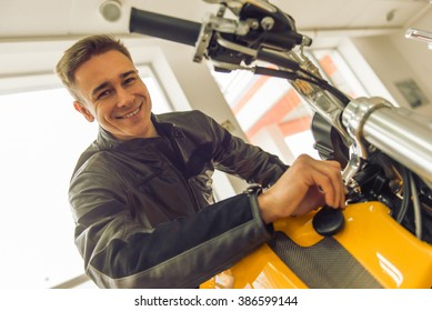 Attractive young blond man in black leather jacket is looking at camera and smiling while examining motorbike