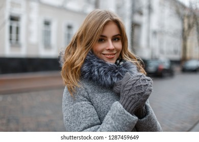 Attractive young blond woman with a beautiful smile in a stylish warm winter outerwear in knitted mittens stands in the city on the background of vintage buildings. Happy fashionable girl.