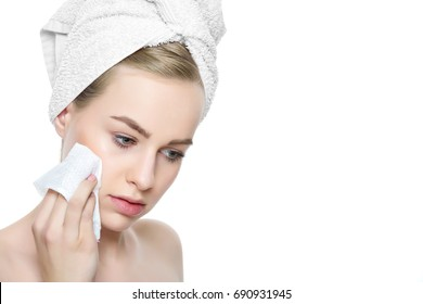 Attractive young blond woman with her hair wrapped in a towel, removing make up. Pretty girl with perfect complexion cleansing her face using soft face wipe. Isolated on white background
