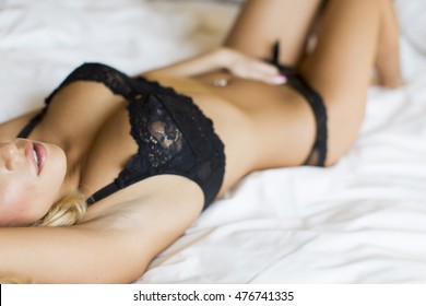 Attractive young blond woman laying on the bed in lingerie