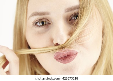 An attractive young blond woman plays with a wisp of her fair hair and drag it around her nose.