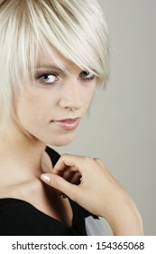 Attractive young blond woman with a thoughtful expression giving the camera a serious look with her hand raised to her throat