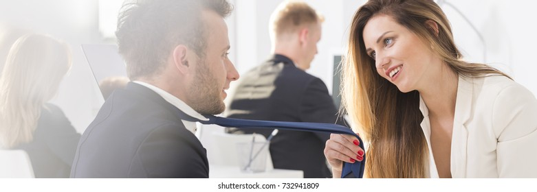 Attractive young and blond woman touches a tie of a handsome man