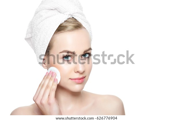 Attractive young blond woman with towel in her hair removing make up. Smiling pretty girl with perfect complexion cleansing her face using soft cosmetic cotton pad.