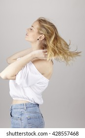 An attractive young blond woman wears summerly clothes (a white blouse and light blue jeans) and enjoys a fresh summer breeze. Studio shot over light gray background.