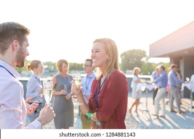 Attractive young blonde business woman having a conversation with her boyfriend as they enjoy a glass of wine on a rooftop restaurant bar after a convention with their office colleagues