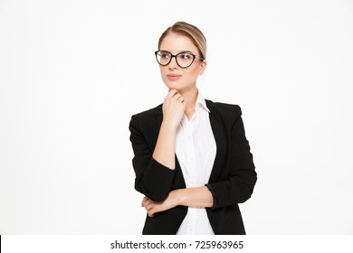Attractive young blonde business woman in eyeglasses holding hand near chin and looking away over white background
