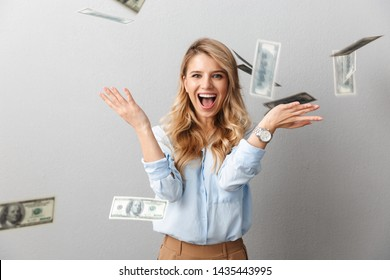 Attractive young blonde businesswoman wearing shirt standing under money banknotes rain isolated over gray background