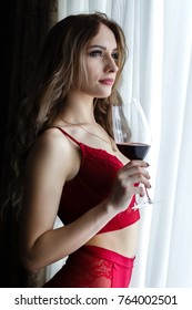 Attractive young blonde girl dressed in a red lingerie  drinks  wine from big wineglass near a  window.