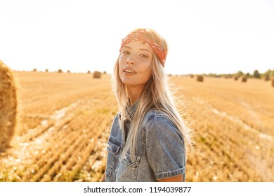 Attractive young blonde girl in headband at the wheat field