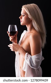 Attractive young blonde girl in lingerie drinks wine