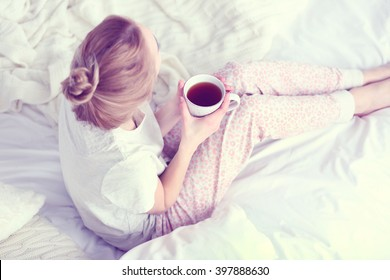 Attractive young blonde girl in a pajamas holding a cup of tea while sitting in white bedding and pillows