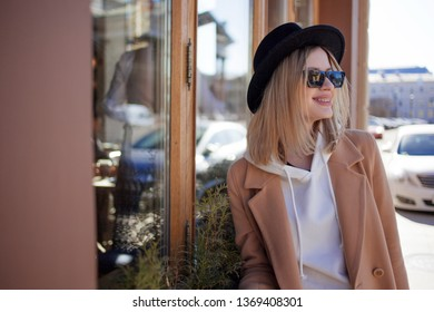 Attractive young blonde in a hat and sunglasses. Young woman outdoors. Happy girl near street cafe