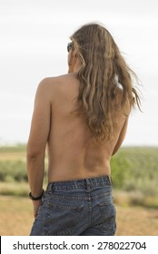 Attractive young blonde man with long hair without shirt
