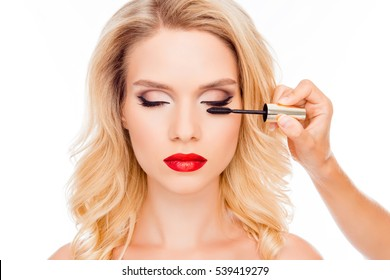 Attractive young blonde with red lips holding brush of mascara
